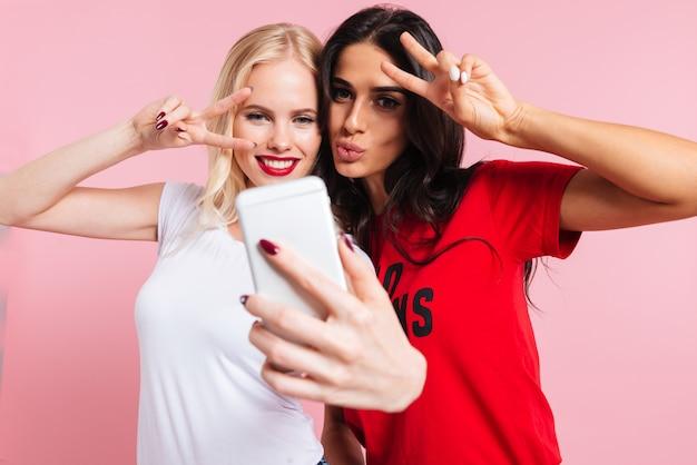 Imagen de dos mujeres muy sonrientes haciendo selfie en teléfono inteligente sobre rosa