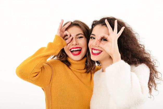 Imagen de dos niñas felices en suéteres divirtiéndose y mostrando gestos bien sobre la pared blanca