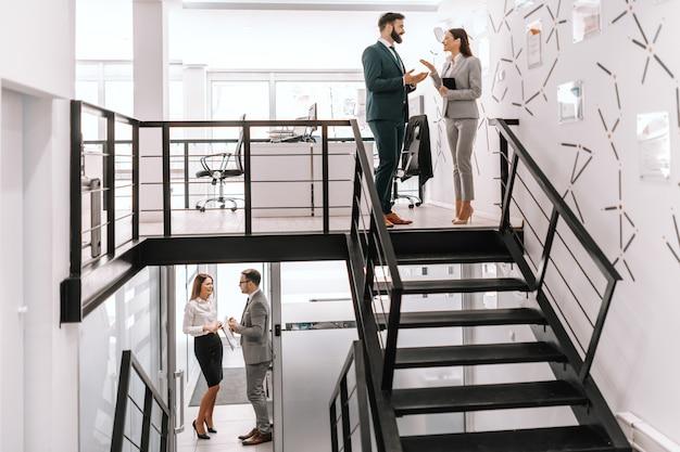 Imagen de dos pares de colegas en ropa formal discutiendo sobre negocios en el lugar de trabajo moderno.