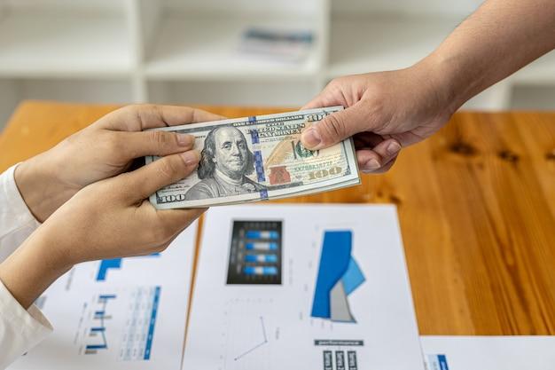 Imagen de dos personas entregando un dólar, son socios comerciales que están cometiendo un comportamiento corrupto al sobornarlos para obtener un beneficio mutuo ilegal. el concepto de fraude y soborno empresarial.
