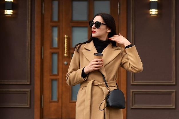Imagen de elegante hermosa mujer de pie afuera