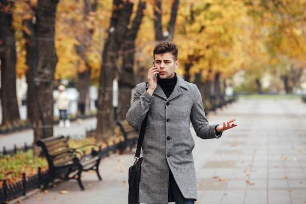 Imagen de elegante hombre con abrigo con bolsa caminando en el parque de la ciudad y hablando por teléfono inteligente en otoño