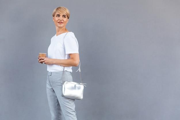 Imagen de elegante mujer rubia con camiseta blanca que se encuentran aisladas sobre una pared gris y mirando a un lado en copyspace con café para llevar