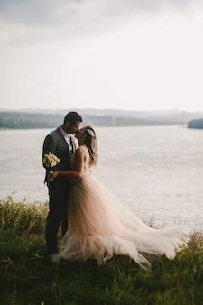 Imagen emocional de la pareja recién casada de pie en el campo y besándose. río en el fondo. objetivos de pareja.