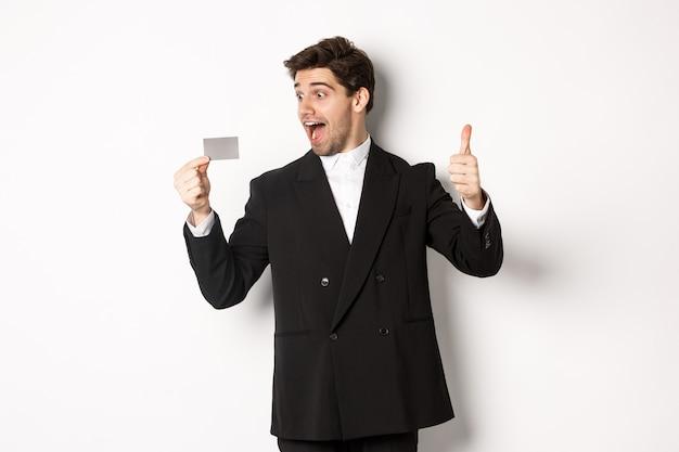 Imagen del empresario guapo emocionado, mostrando la tarjeta de crédito y el pulgar hacia arriba, de pie contra el fondo blanco.
