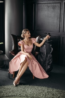 Imagen de una encantadora dama caucásica sentada en el sillón de cuero negro y posa para la cámara