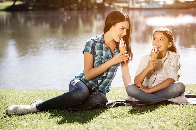 Imagen encantadora de madre e hija sentadas juntas cerca del lago y comiendo helado. mujer joven busca y niña. kid está sentado con las piernas cruzadas y mirando a mamá.
