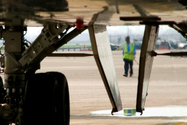 Imagen del equipo de tierra del aeropuerto detrás del tren de aterrizaje de un avión.