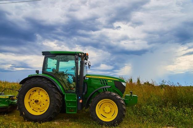 Imagen del equipo del tractor agrícola john deer con nubes tormentosas