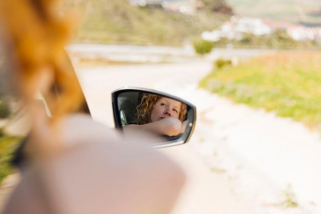 Imagen de espejo de mujer montando en carro.