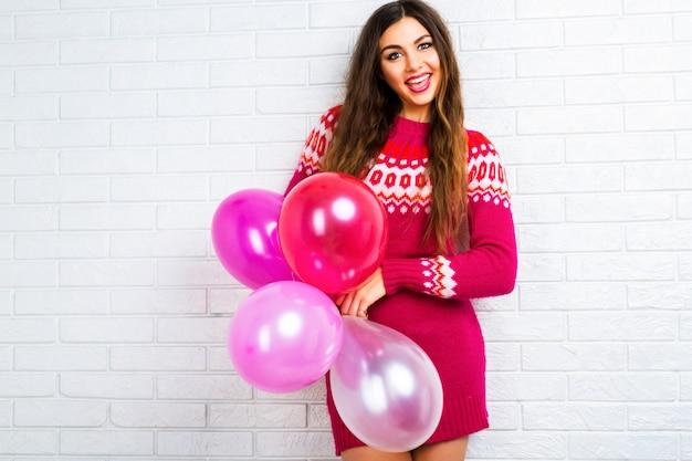 Imagen de estilo de vida interior de una divertida chica morena bonita con maquillaje brillante y pelos largos, vistiendo un suéter moderno y sosteniendo globos de fiesta rosa.