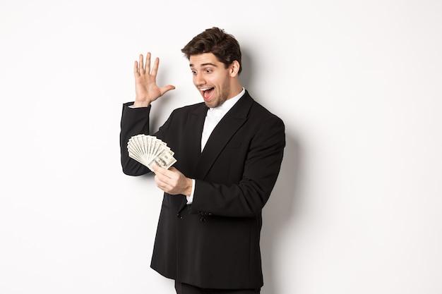 Imagen del exitoso hombre de negocios en traje negro, mirando el dinero y triunfando, ganando dinero en efectivo, de pie sobre fondo blanco.