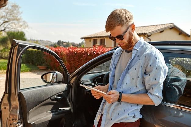 Imagen exterior de chico guapo hipster de moda con barba borrosa de pie en su coche