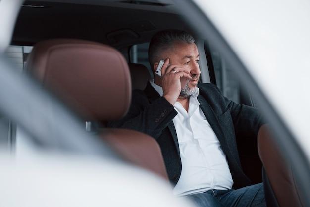 Imagen desde el exterior del vehículo. tener una llamada de negocios mientras está sentado en la parte trasera del automóvil de lujo moderno