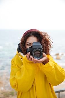 Imagen de feliz fotógrafo rizado africano joven vistiendo abrigo amarillo con cámara y caminando al aire libre