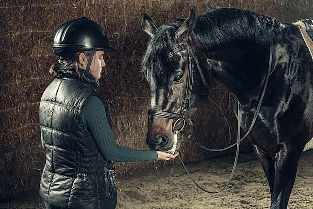 Imagen de feliz hembra de pie cerca de caballo de raza pura