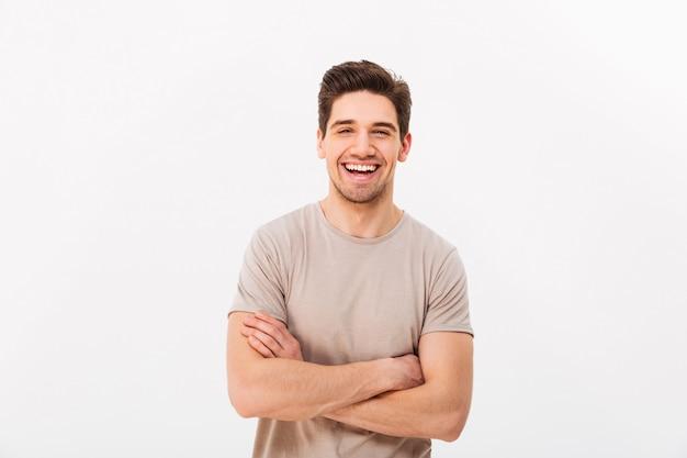 Imagen de feliz hombre sonriente 30s con cerdas posando en la cámara con las manos cruzadas, aislado sobre la pared blanca