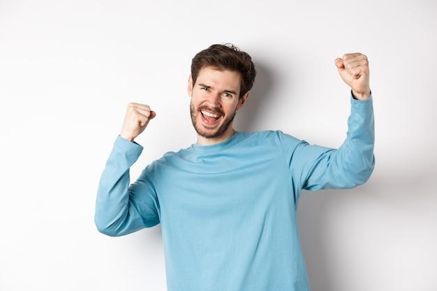 Imagen de feliz joven triunfando, sintiéndose campeón, ganando y gritando de alegría, de pie sobre fondo blanco.