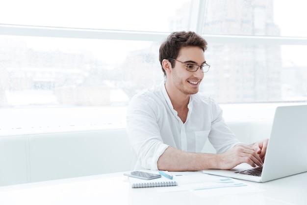 Imagen de feliz joven vestido con camisa blanca con ordenador portátil. mira la computadora portátil.