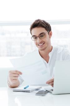 Imagen de feliz joven vestido con camisa blanca con ordenador portátil. sosteniendo documentos.
