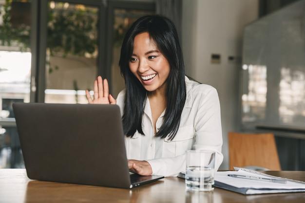 Imagen de feliz mujer asiática de 20 años con camisa blanca sonriendo y agitando la mano en la computadora portátil, mientras habla o charla en una videollamada en la oficina