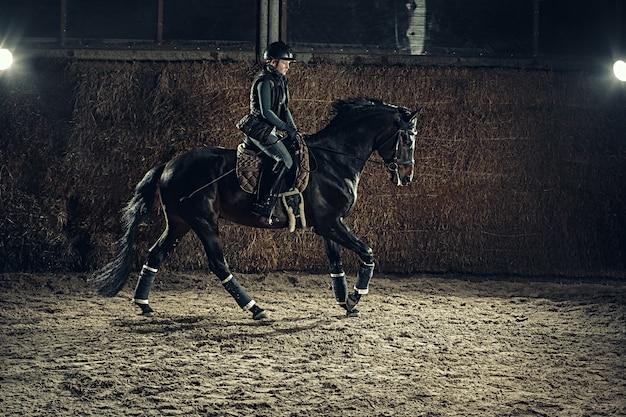 Imagen de feliz mujer sentada en caballo de raza pura