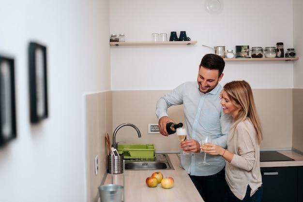 Imagen de la feliz pareja con copas de vino, verter el vino.