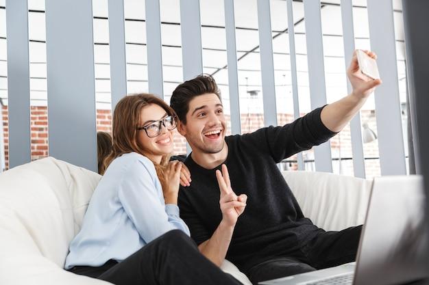 Imagen de una feliz pareja de enamorados jóvenes en casa en el interior con ordenador portátil hacer un selfie por teléfono.