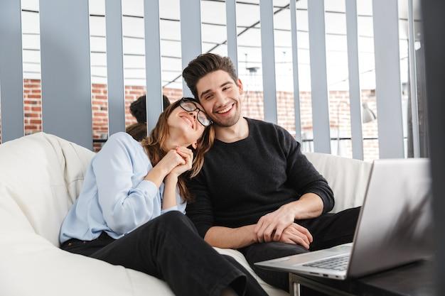 Imagen de una feliz pareja de enamorados jóvenes en casa en el interior con ordenador portátil.