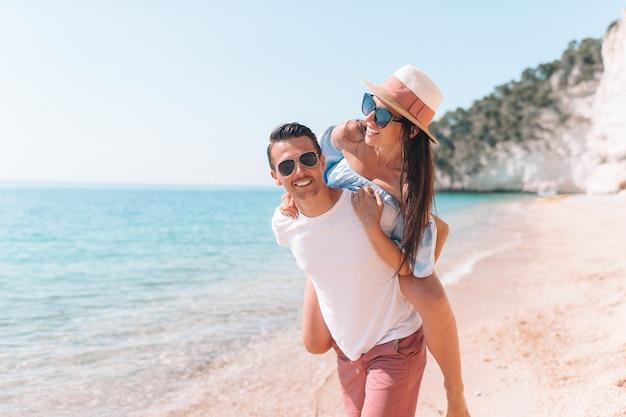 Imagen de la feliz pareja en gafas de sol en la playa