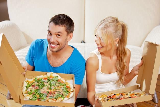 Imagen de la feliz pareja romántica comiendo pizza en casa (enfoque en el hombre)