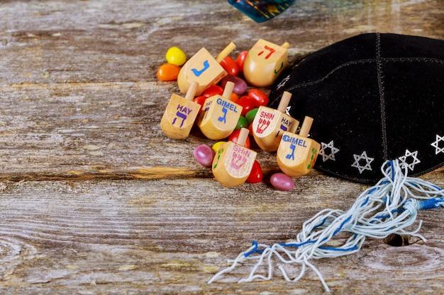 Imagen de la fiesta judía de jánuca con trompo de madera dreidel en el fondo de brillo
