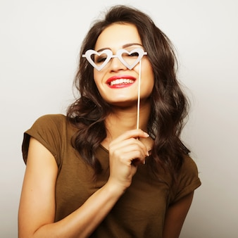 Imagen de fiesta. juguetón joven sosteniendo una fiesta gafas.