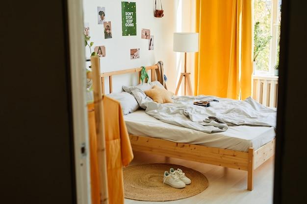 Imagen de fondo del acogedor interior del dormitorio adolescente a la luz del sol con una gran cantidad de accesorios y una cama cómoda, espacio de copia