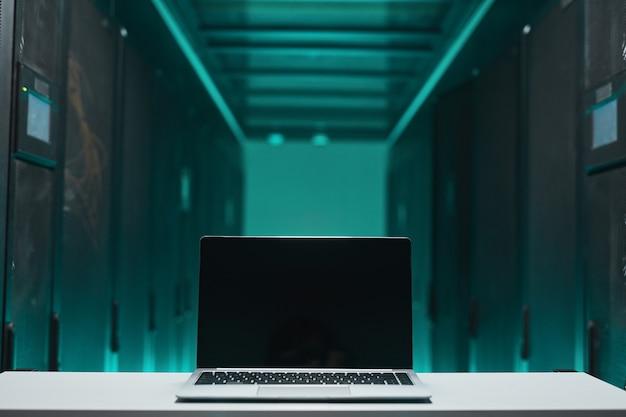 Imagen de fondo de la computadora portátil abierta con pantalla en blanco en la sala de servidores futurista, concepto de supercomputadora, espacio de copia