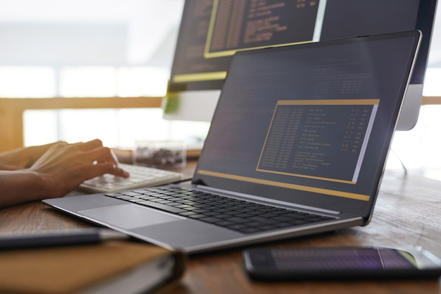 Imagen de fondo de manos masculinas escribiendo en el teclado con código de programación negro y naranja en la pantalla del portátil en primer plano, concepto de desarrollador de ti, espacio de copia