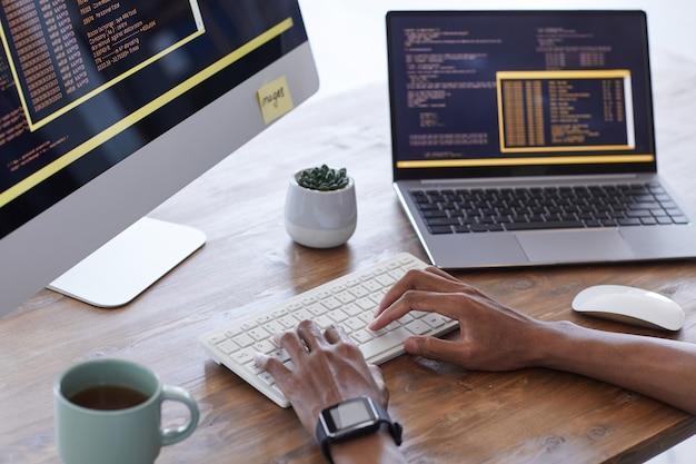Imagen de fondo de manos masculinas escribiendo en el teclado mientras se trabaja en código de computadora en el estudio de desarrollo de ti, espacio de copia