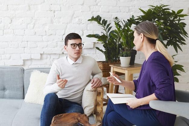 Imagen de frustrado joven caucásico vestido con suéter y anteojos sentado en un cómodo sofá, compartiendo sus problemas personales con una consejera de mediana edad durante la sesión de terapia