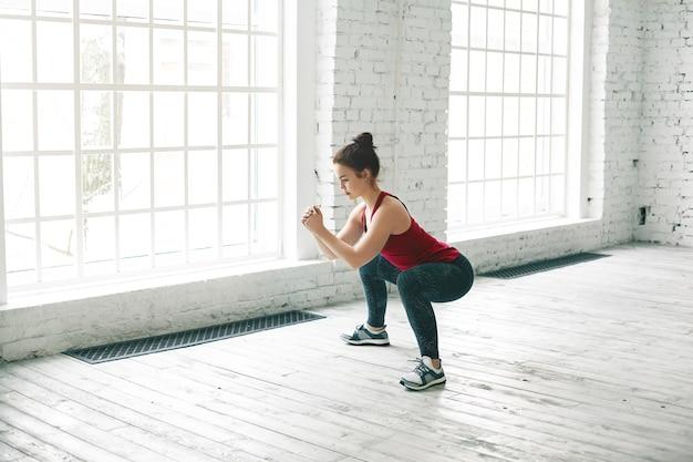 Imagen de fuerte chica deportiva vistiendo elegante camiseta sin mangas, zapatillas y leggings haciendo sentadillas sobre un piso de madera en el centro de gimnasio contra grandes ventanales