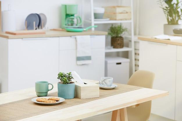 Imagen de galletas y tazas de café o té en la mesa de madera en la cocina
