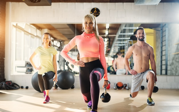 Imagen de una gente en una clase de gimnasia haciendo sentadillas con una pierna con campanas de caldera en sus manos.