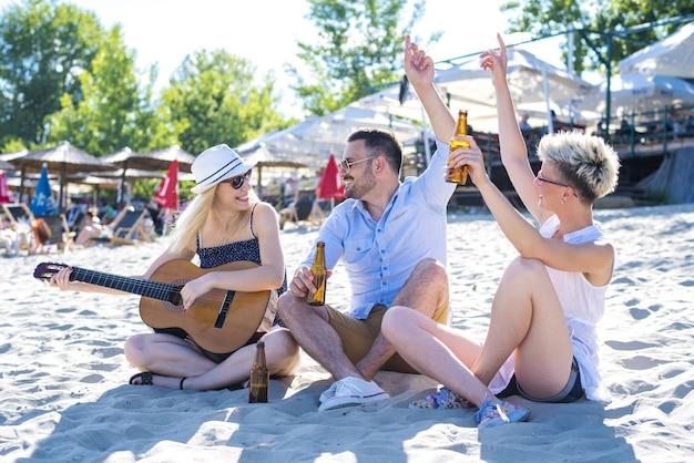 Imagen de gente feliz con una guitarra y una cerveza en la playa.
