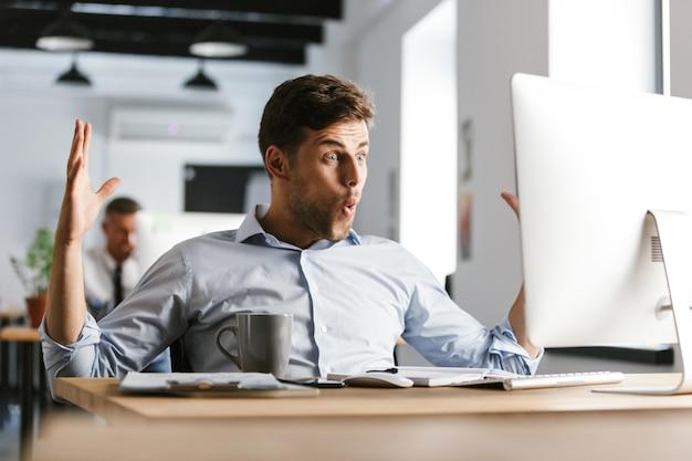 Imagen del gerente masculino feliz sorprendido usando computadora