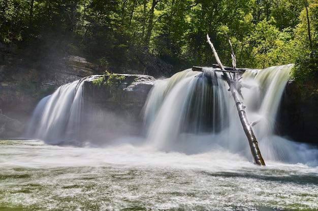Imagen de una gran cascada triple cortando acantilados en el bosque