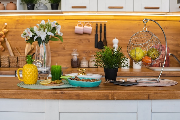 Imagen de la gran cocina luminosa con alacenas blancas y marrones con tetera de piña amarilla, molinillo de pimienta blanca y colgante de metal con frutas y galletas