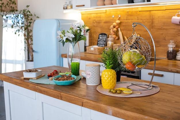 Imagen de la gran cocina luminosa con alacenas blancas y marrones con tetera de piña amarilla, molinillo de pimienta blanca y colgantes de metal con frutas