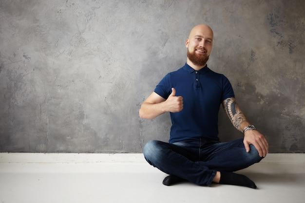 Imagen de guapo joven positivo calvo barbudo con tatuaje en su brazo musculoso sonriendo ampliamente y haciendo gesto de pulgar hacia arriba, teniendo un gran día, estando de buen humor, mostrando aprobación