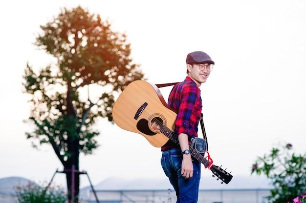 La imagen de un guitarrista de pie feliz mirando el éxito de la música