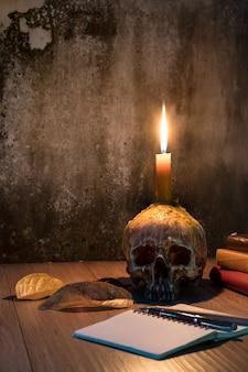 Imagen de halloween con una vela ardiente en una antigua cráneo humano y libros de madera bac tabla