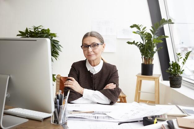 Imagen de la hermosa arquitecta caucásica senior de pelo gris con gafas sonriendo y manteniendo los brazos cruzados, descansando después de que terminó de dibujar un gran proyecto arquitectónico